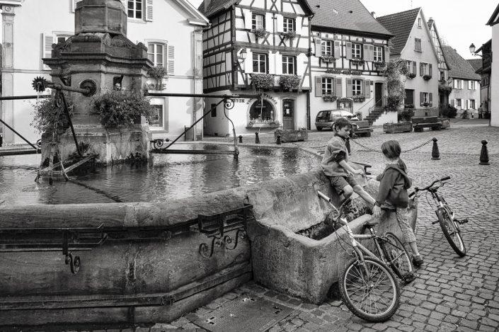 enfants-velo-fontaine-alsace-noir-et-blanc